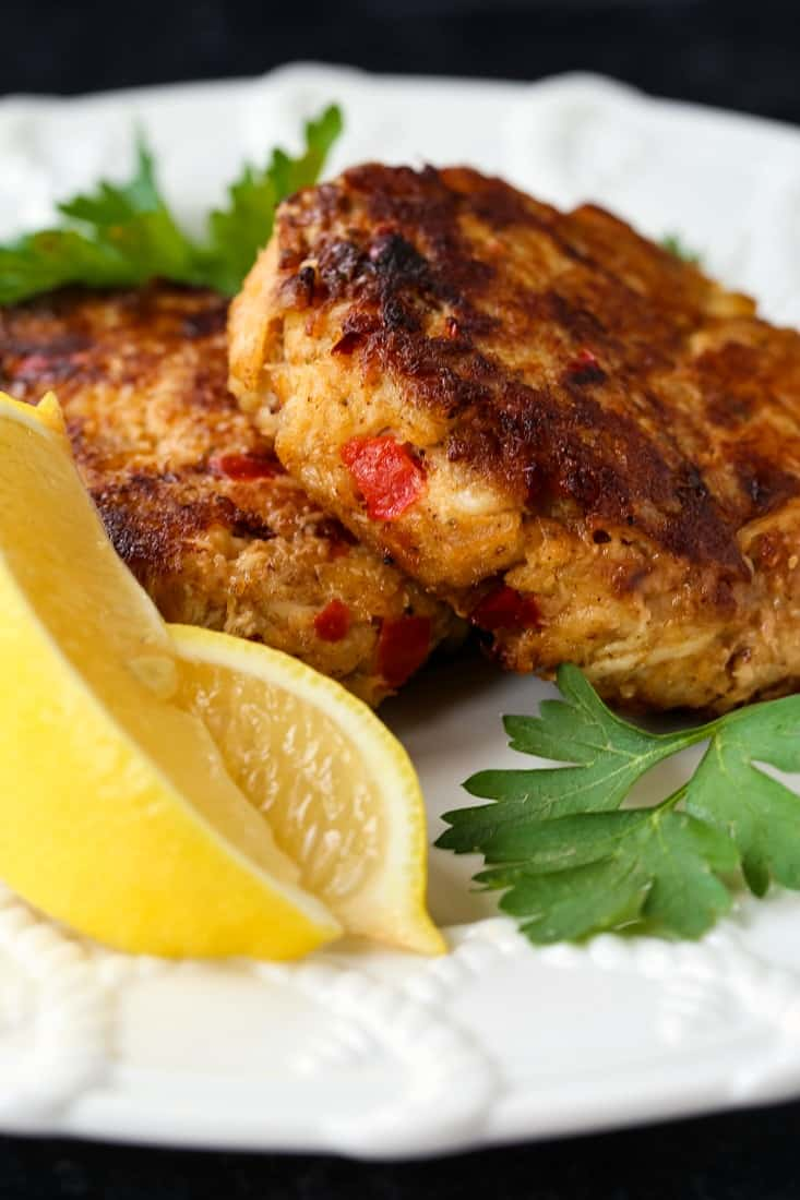 excellent crab cakes on a white plate with sliced lemons
