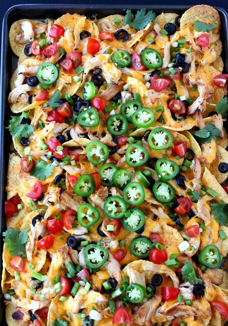 sheet pan chicken nachos with toppings from the top view
