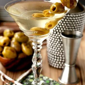 Grilled Dirty Martini in glass with shaker and olives and cocktail napkin
