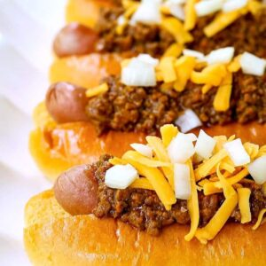 Chili dogs with hot dogs stacked on a platter