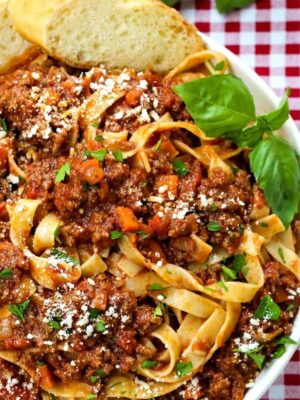 pasta with meat sauce in a white bowl with basil