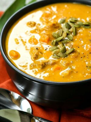 pumpkin sausage soup in a black bowl with pumpkin seeds