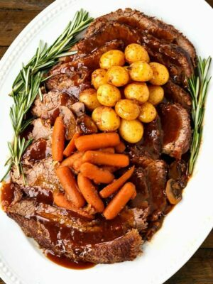 Pot roast recipe on a platter with vegetables is a perfect sunday dinner