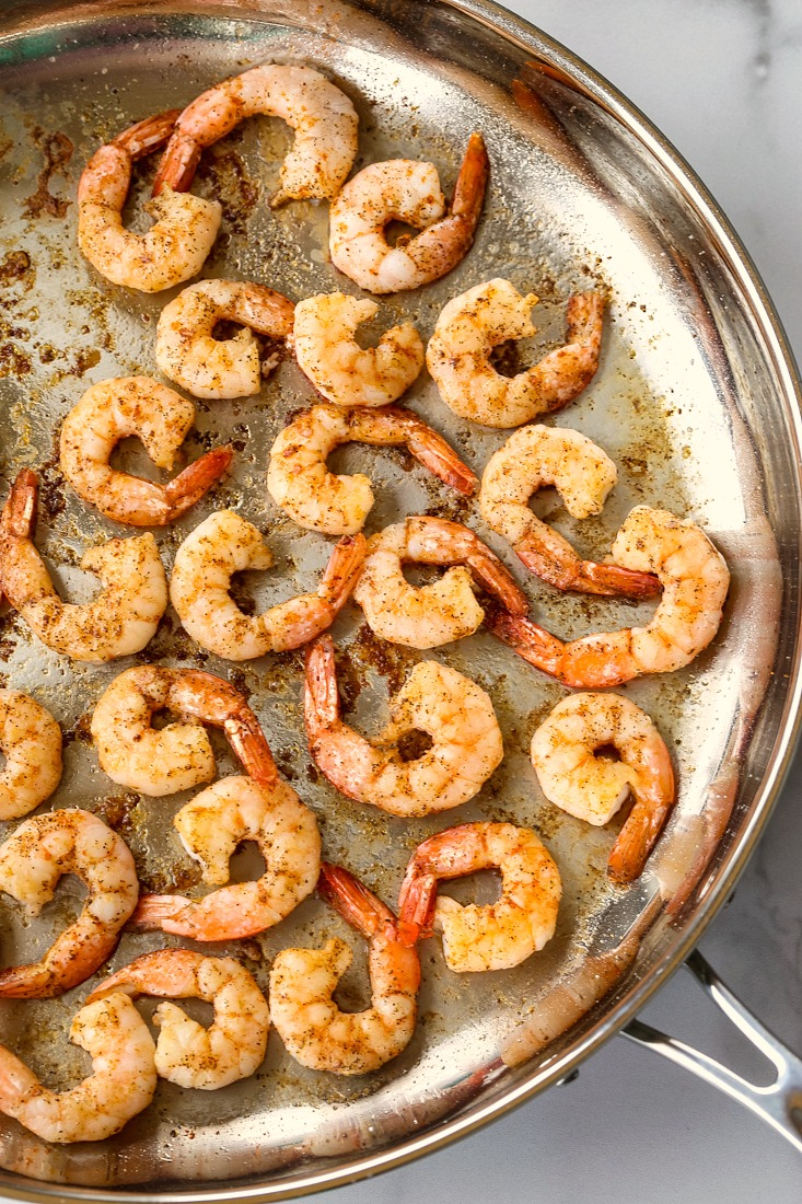 shrimp in a skillet on a marble board