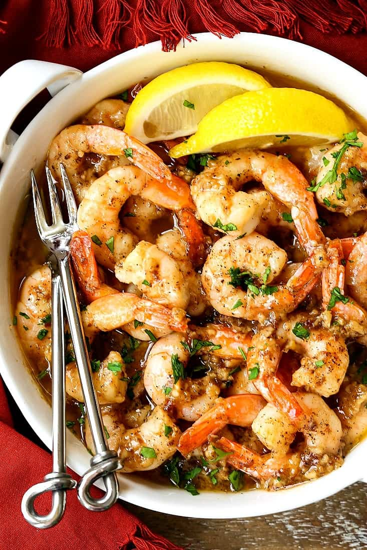garlic butter shrimp in a white crock with forks