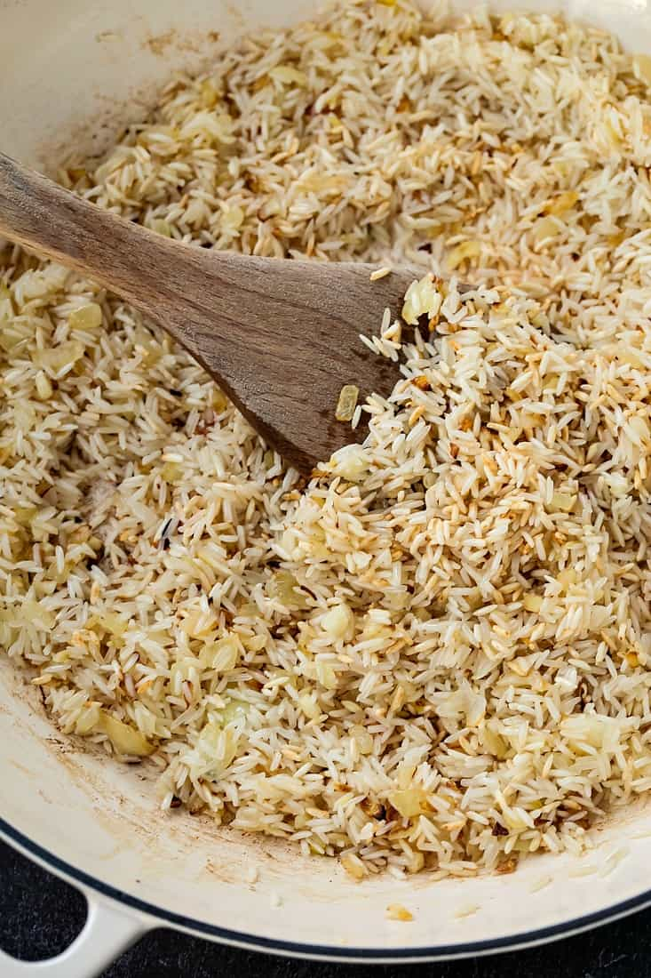 Spanish Rice recipe being browned in butter and onion
